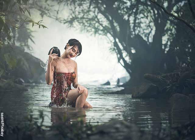 Foto de una mujer mojándose en un río con un recipiente que muestra lo que es soñar con bañarse