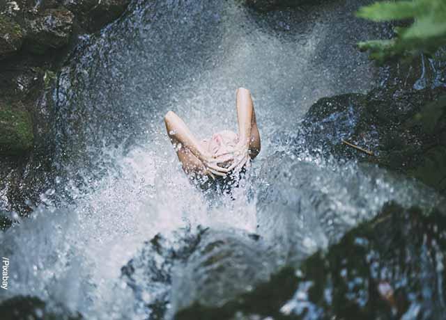Foto de una persona bañándose en una cascada