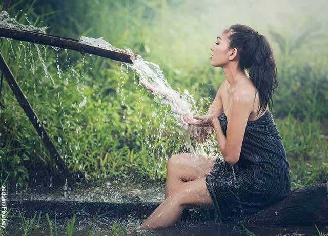 Foto de una mujer sentada recibiendo agua de un tubo natural