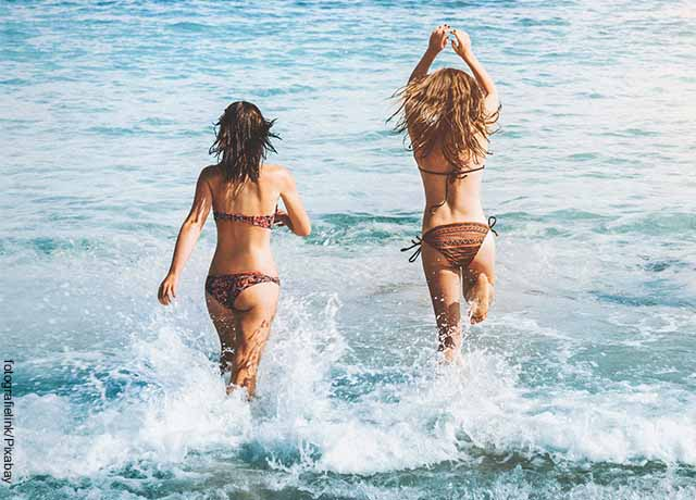 Foto de dos mujeres entrando al mar juntas