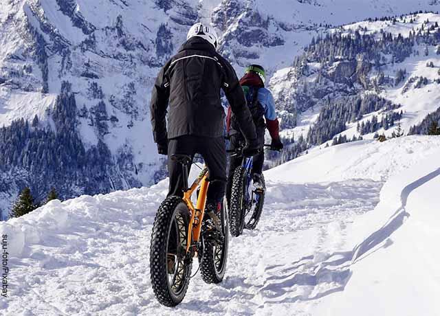 Foto de dos personas montando en bicicleta en la nieve