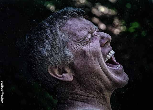 Foto de un hombre mayor gritando bajo la lluvia