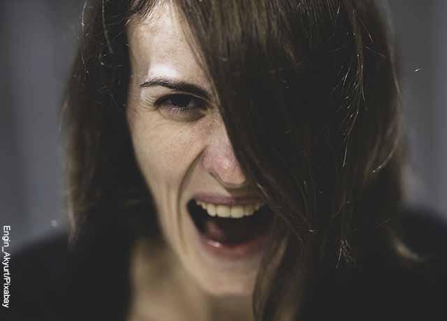 Foto de una mujer gritando asustada que muestra lo que es soñar con disparos