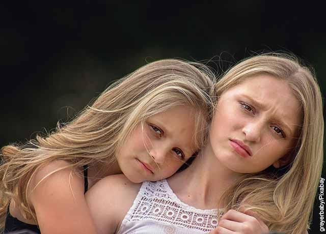 Foto de dos niñas abrazadas haciendo mala cara