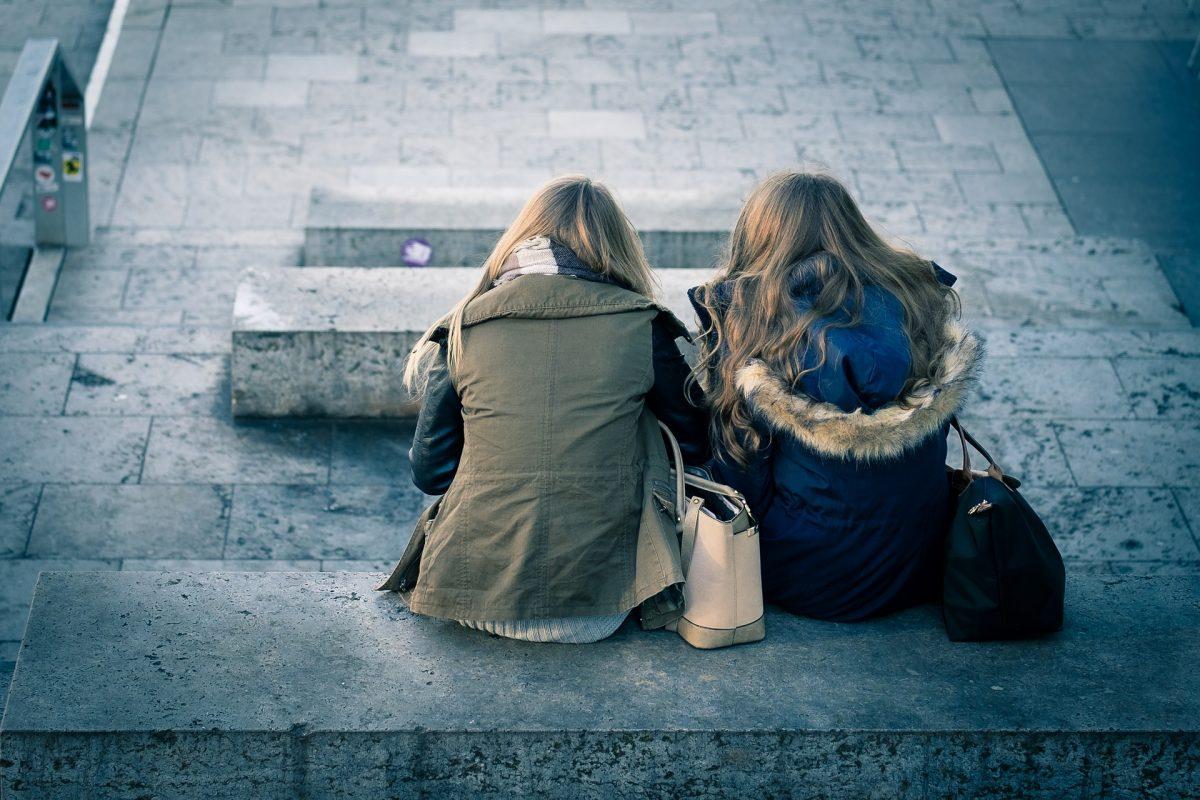 Foto de dos chicas sentadas de espalda en unas escaleras
