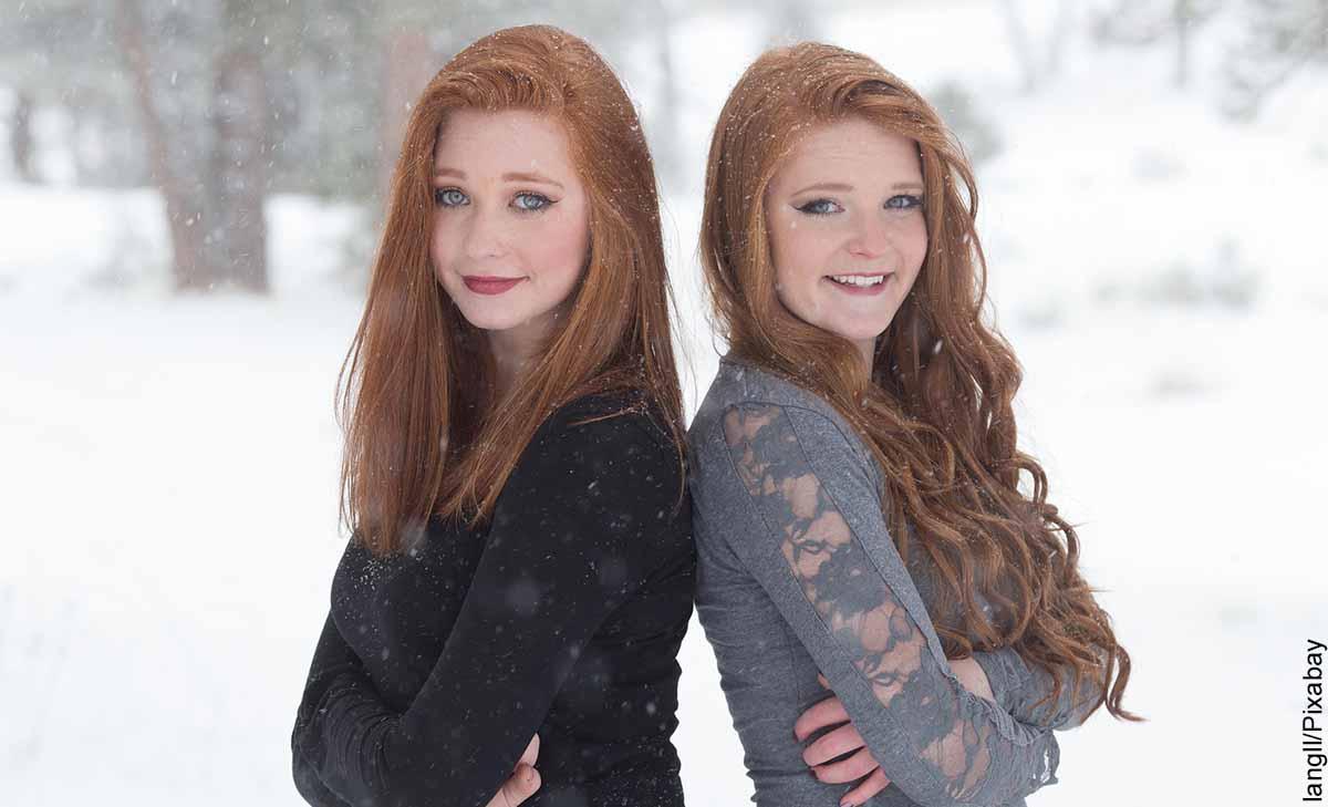 Foto de dos mujeres paradas espalda con espalda que revela lo que es soñar con una hermana