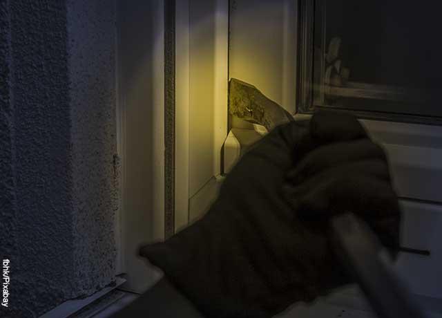 Foto de una mano con guante abriendo una puerta que muestra lo que es soñar con ladrones
