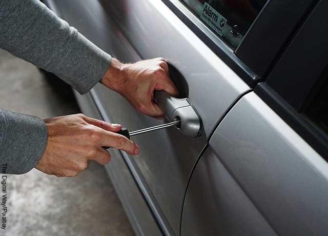 Foto de una persona abriendo la puerta de un carro gris