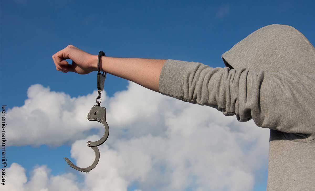 Foto de un hombre liberándose de esposas que revela lo que es soñar con ladrones