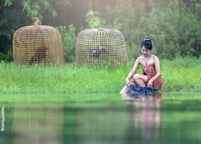 Foto de una mujer lavando ropa en el río