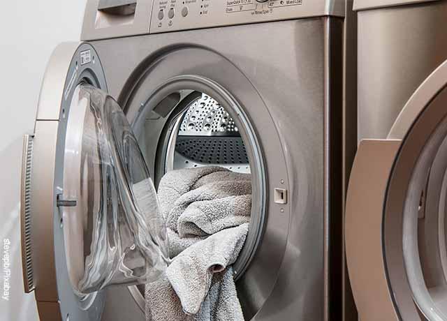 Foto de una lavadora abierta con una toalla que revela lo que es soñar con lavar ropa
