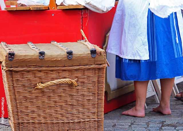 Foto de una mujer lavando ropa y una canasta para meter la ropa