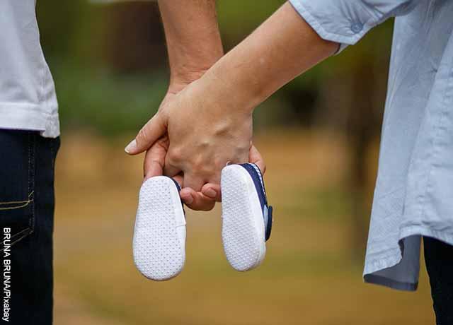 Foto de una pareja tomada de las manos con unos zapatos de bebé que muestra lo que es soñar con parto