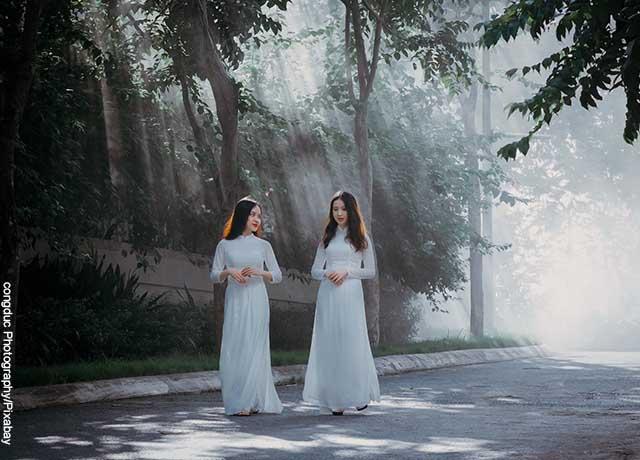 Foto de dos mujeres vestidas de blanco caminando