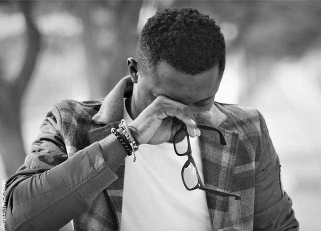 Foto de un hombre que se quita las gafas y llora