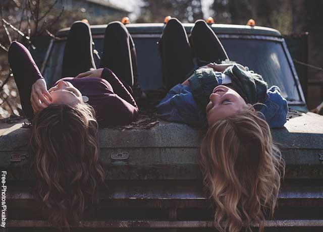 Foto de dos mujeres acostadas sobre un carro que muestran lo que es soñar con un amigo muerto