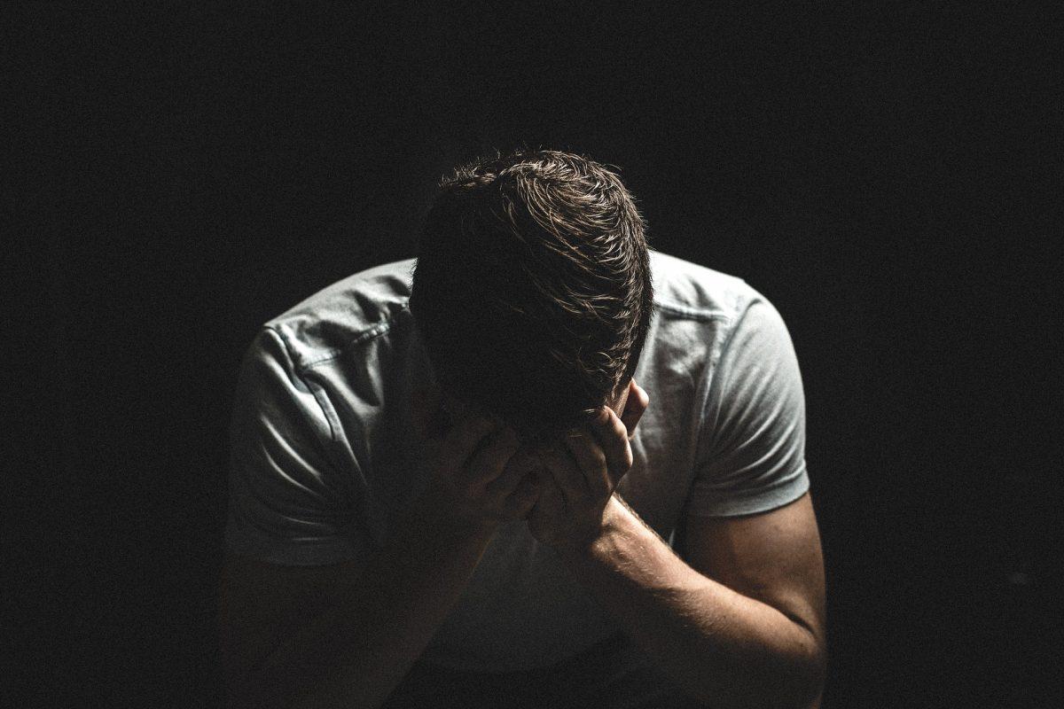Foto de un hombre sentado que toma su cabeza