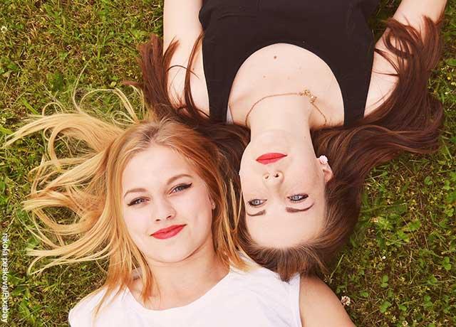 Foto de dos mujeres acostadas sobre el pasto