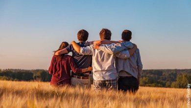 Foto de 4 amigos abrazados de espalda que muestra lo que es soñar con un amigo muerto