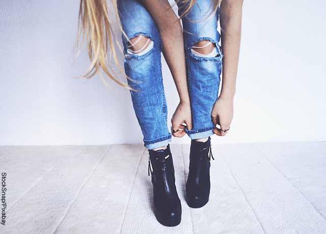 Foto de una mujer arreglando su bota del jean que muestra lo que es soñar con zapatos nuevos