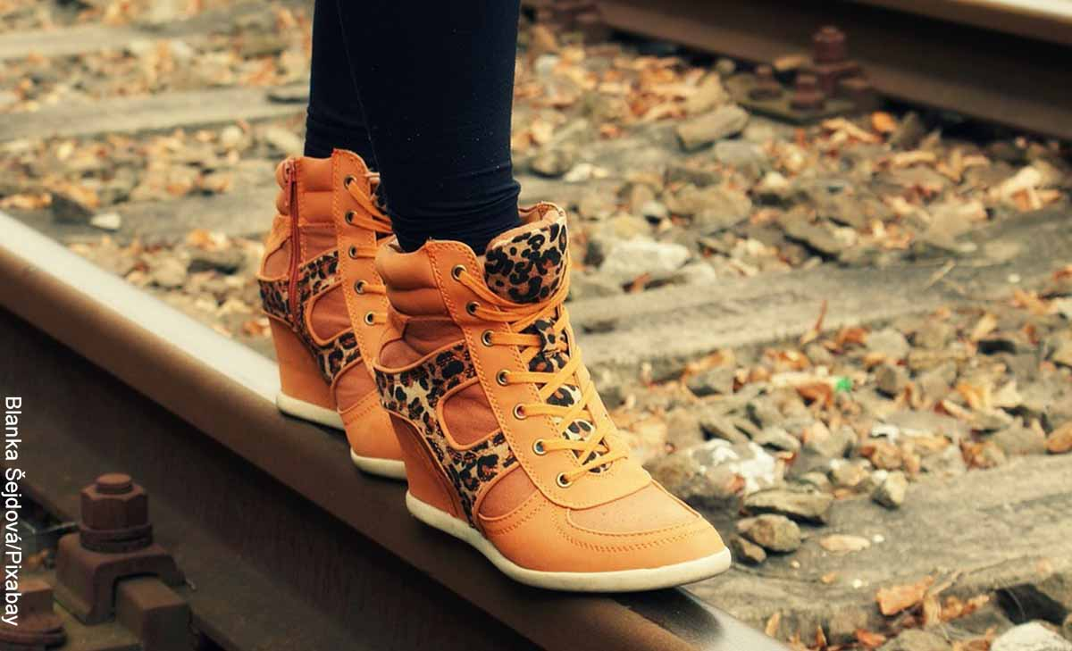 Foto de una mujer caminando por la carrilera que revela lo que es soñar con zapatos nuevos