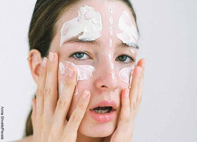 Foto de una mujer aplicando crema sobre su rostro