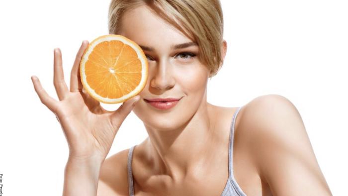 Foto de una mujer con una naranja