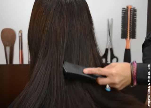 Foto de una mujer a la que están peinando con un cepillo