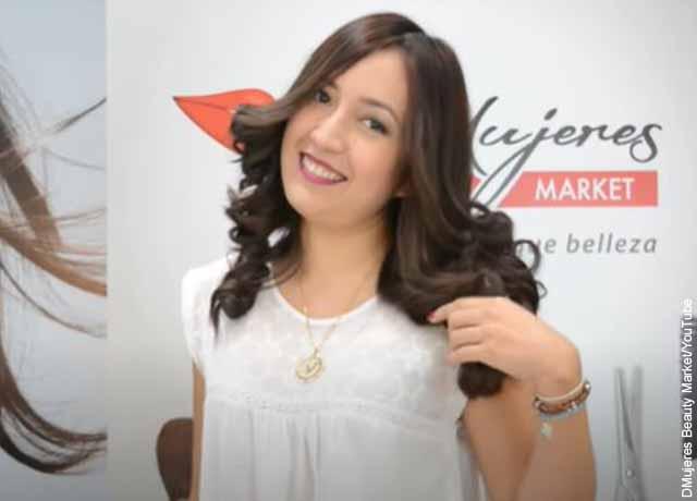 Foto de una mujer sonriente que muestra su pelo crespo