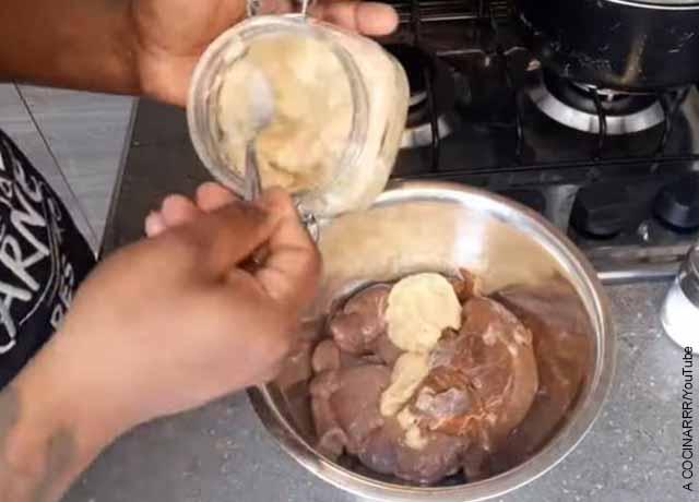 Foto de una persona adobando carne