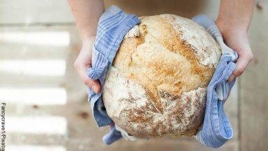 Foto de una persona sosteniendo una masa horneada que revela cómo hacer pan casero