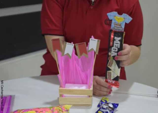 Foto de una caja de madera con papel y chocolatinas