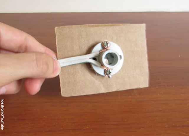 Foto de una mano sosteniendo una extensión y una roseta de bombillo