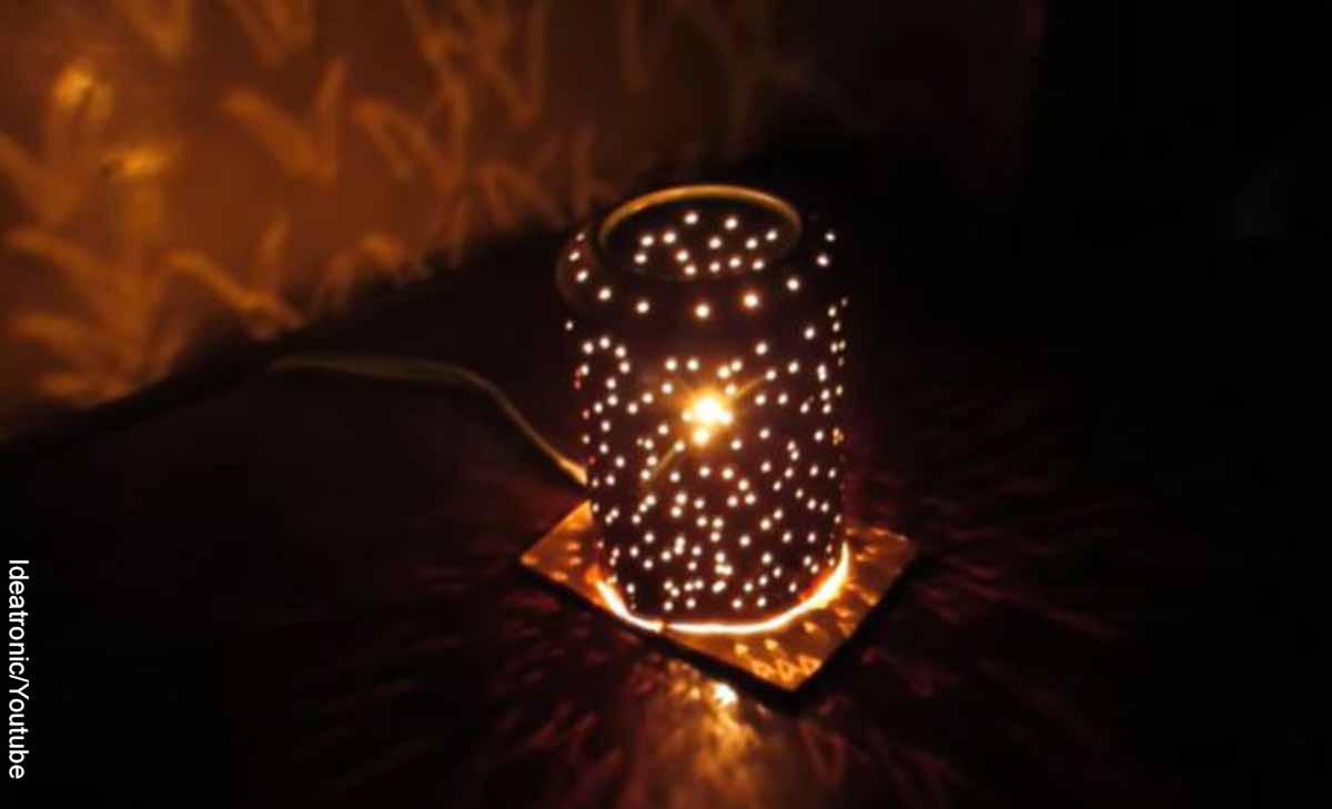 Foto de una lata atravesada con agujeros y un bombillo que revela cómo hacer una lámpara casera