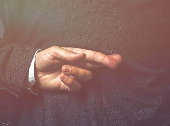 Foto de la mano de un hombre cruzando los dedos en su espalda