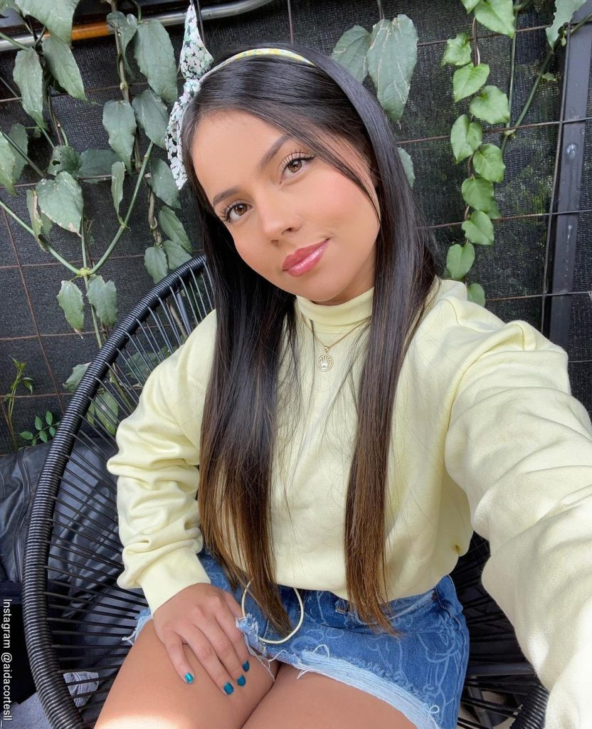 Foto de Aida Cortés sentada con una falda de jean