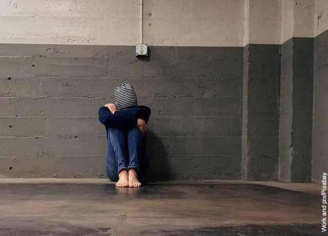 Foto de una mujer sentada llorando en una sala que muestra las frases para pedir perdón a tu pareja