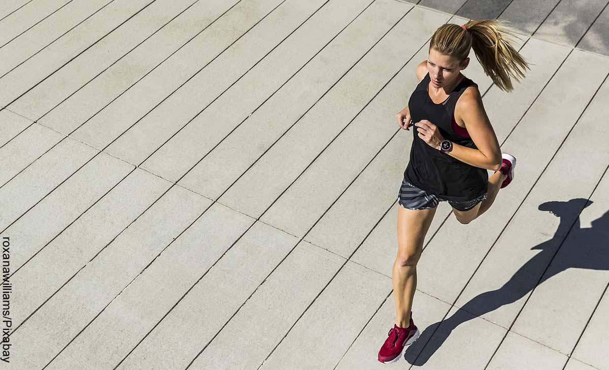 Foto de una mujer corriendo por una vía que revela la glutamina para qué sirve