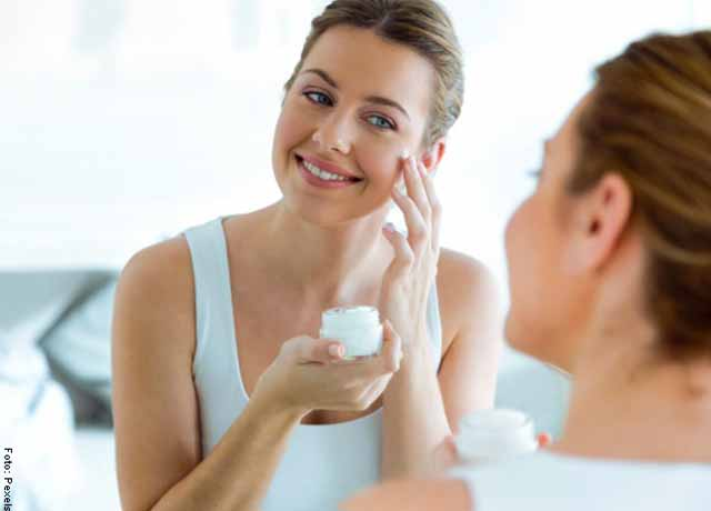 Foto de una mujer aplicando crema en los pómulos