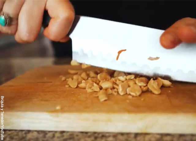 Foto de una persona cortando maní