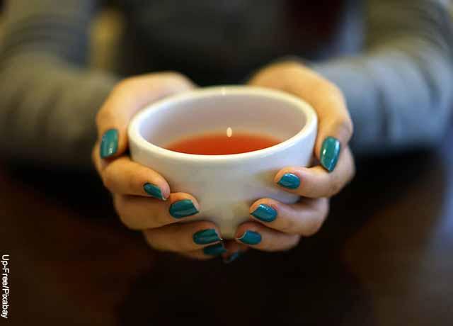 Foto de una mujer sosteniendo una taza que muestra para qué sirve el aceite de oliva con limón