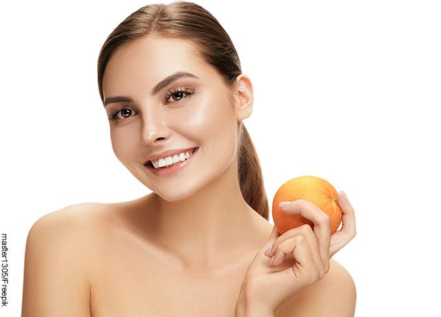 Foto de una mujer sonriendo y mostrando una manzana