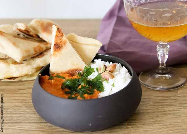 Foto de un plato de comida india con pan y un guiso