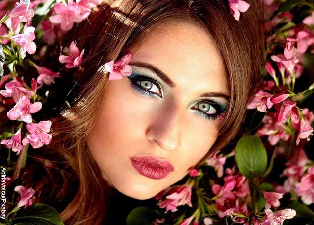 Foto del rostro de una modelo entre flores rosadas