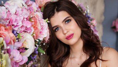 Foto del rostro de una mujer joven entre flores que revela para qué sirve el colágeno
