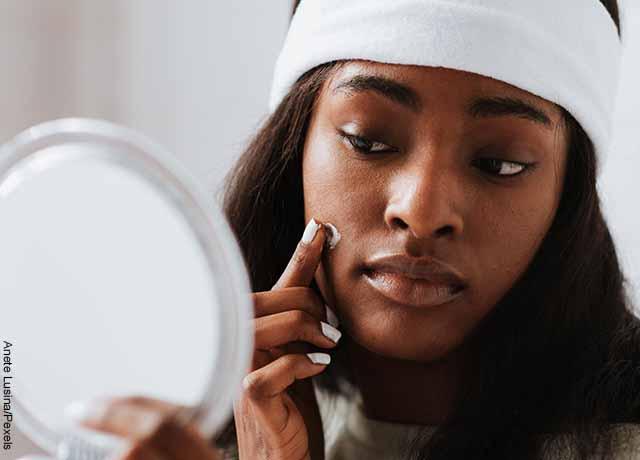 Foto de una mujer aplicando crema en su piel mirándose al espejo