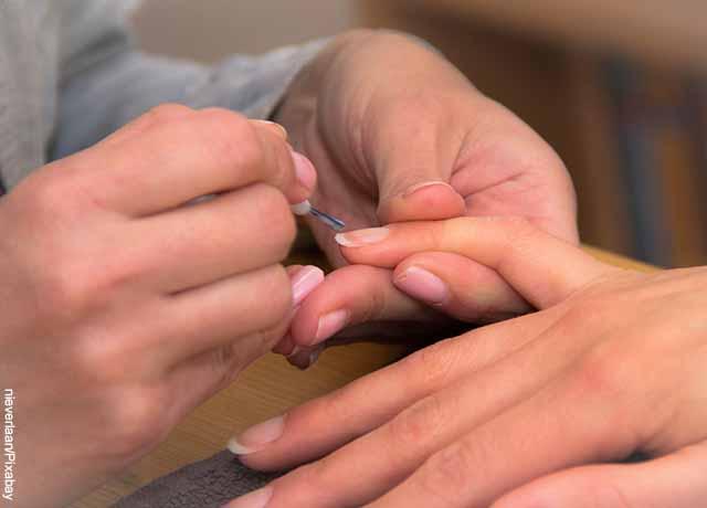 Foto de una persona arreglándose las uñas de las manos