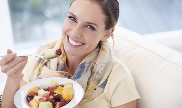 Foto de mujer comiendo fruta