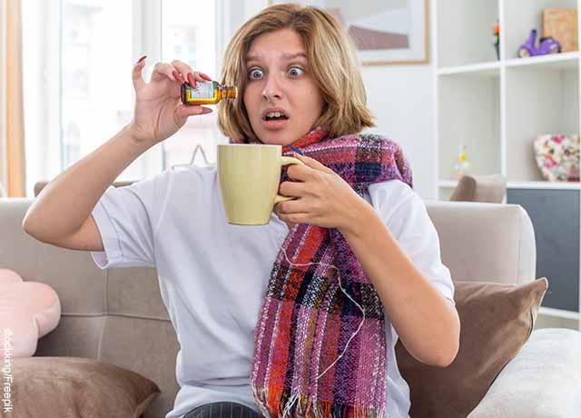 Foto de una mujer aplicando gotas a una bebida