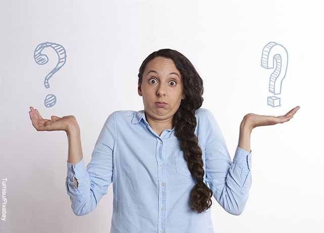 Foto de una mujer con dos signos de pregunta en sus manos